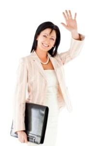 Smiling businesswoman with briefcase waving hand, looking at camera